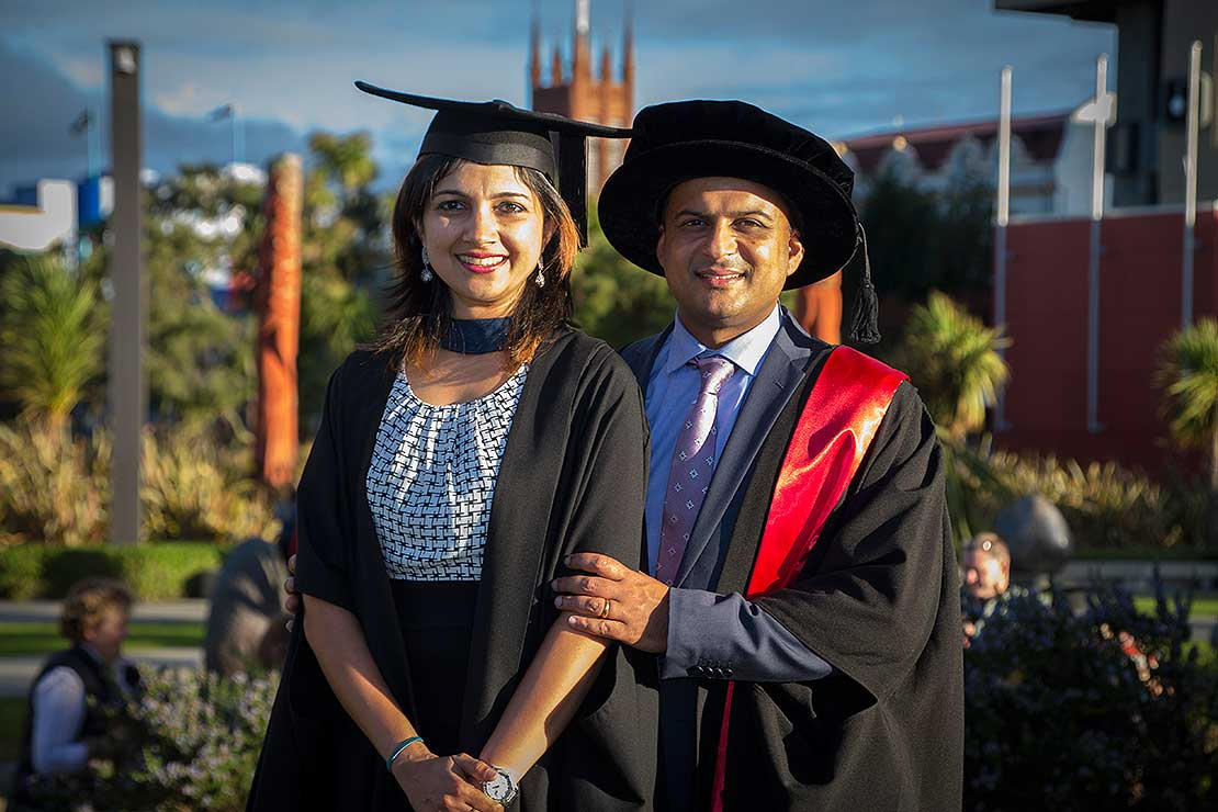 Amit and Namrata Taneja together outdoors on campus, wearing graduation caps and gowns